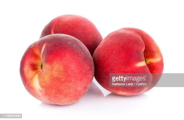 close-up of peaches against white background - peach stock pictures, royalty-free photos & images