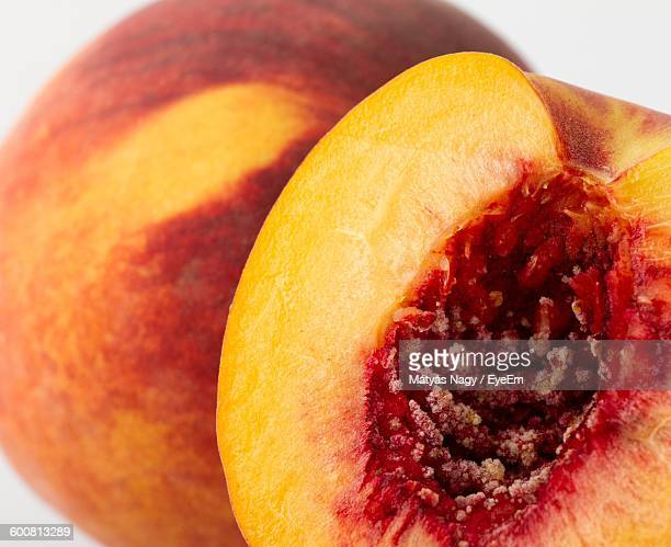 Close-Up Of Peaches On Table Against White Background