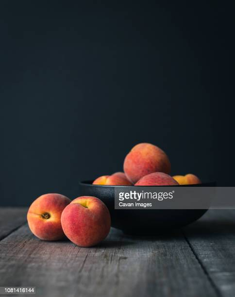 close-up of peaches on wooden table against black background - 果物の盛り合わせ ストックフォトと画像