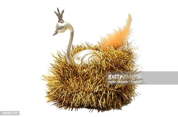 Close-Up Of Peacock Figurine In Tinsel Over White Background