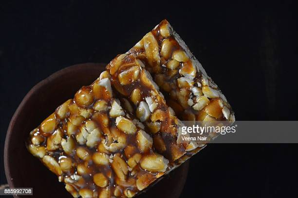 close-up of peanut brittle/chikki in a clay bowl-indian snack - makar sankranti stock pictures, royalty-free photos & images