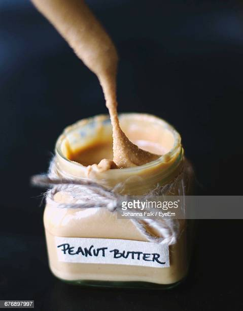 Close-Up Of Peanut Butter In Jar Against Black Background