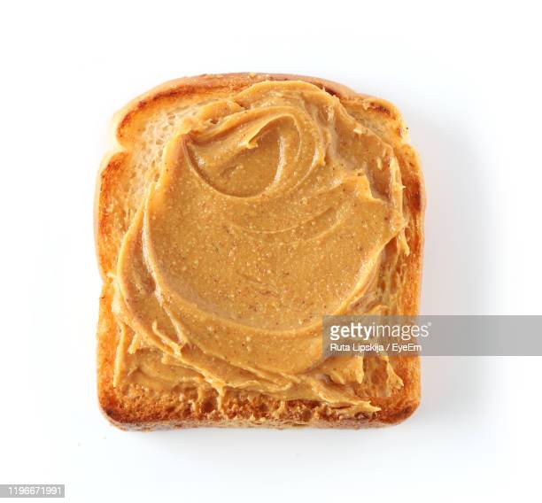 close-up of peanut butter on toasted bread over white background - toasted bread stock pictures, royalty-free photos & images