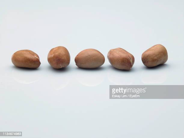 close-up of peanuts against white background - small group of objects stock pictures, royalty-free photos & images