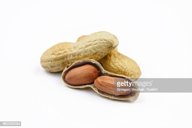 close-up of peanuts against white background - peanuts stockfoto's en -beelden