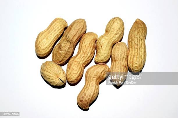 close-up of peanuts over white background - peanuts stockfoto's en -beelden