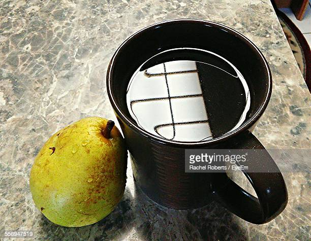 Close-Up Of Pear And Black Tea On Table