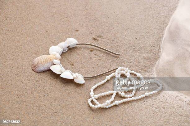 Close-Up Of Pearl Necklace By Seashell Headband On Sand At Beach