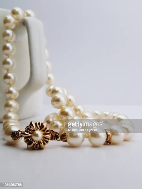 close-up of pearl necklace in mug on table - accessoires stock-fotos und bilder