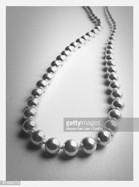 Close-up of pearl necklace over white background
