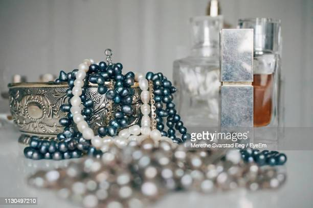 close-up of pearl necklaces and perfumes on table - jewelry box stock pictures, royalty-free photos & images