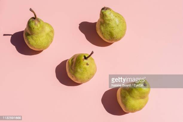 close-up of pears over peach background - pear stock pictures, royalty-free photos & images