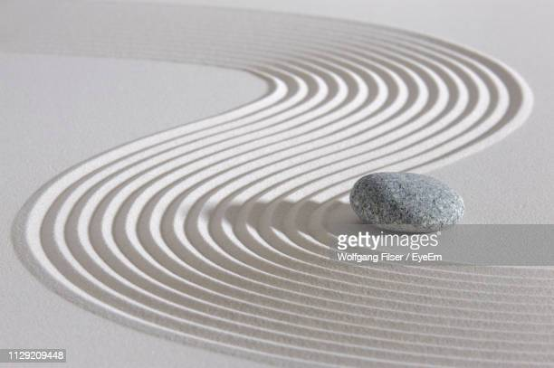 close-up of pebble on sand at beach - kalmte stockfoto's en -beelden