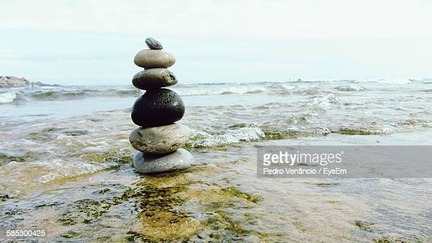 Close-Up Of Pebble Stack In Shore Against Sky