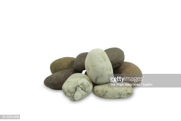 close-up of pebbles against white background - pebble stock photos and pictures