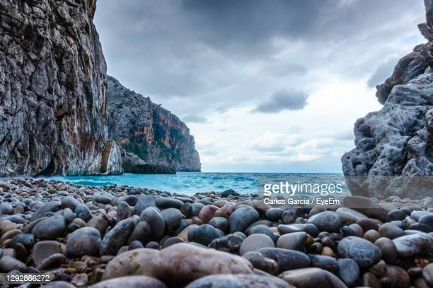 close-up of pebbles at beach against sea and sky - manacor stock pictures, royalty-free photos & images