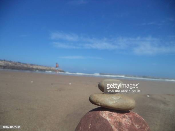 close-up of pebbles on beach against sky - ismail khairdine stock photos and pictures