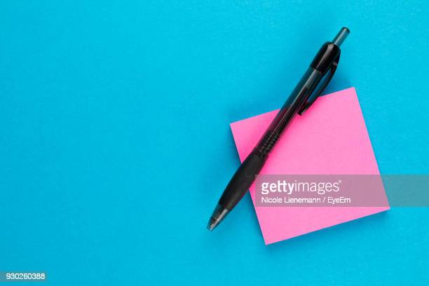 close-up of pen and pink paper against blue background - adhesive note stock pictures, royalty-free photos & images
