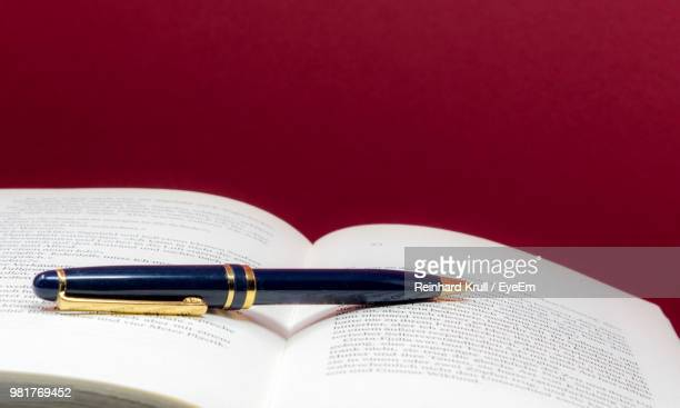 Close-Up Of Pen On Open Book Against Red Wall