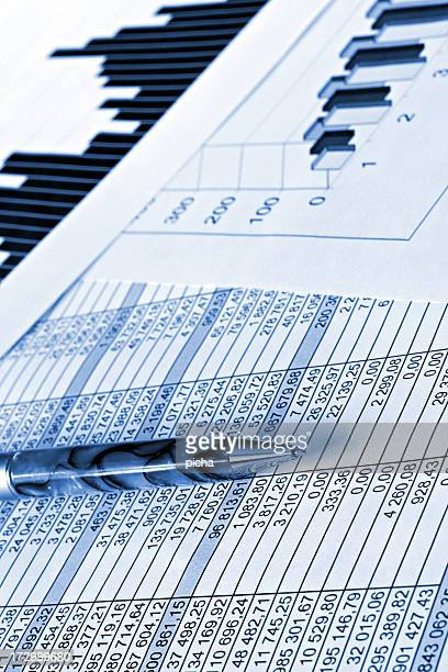 Close-up of pen over stack of financial documents