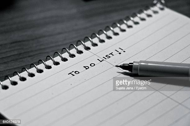 Close-Up Of Pen With Text On Note Pad At Table