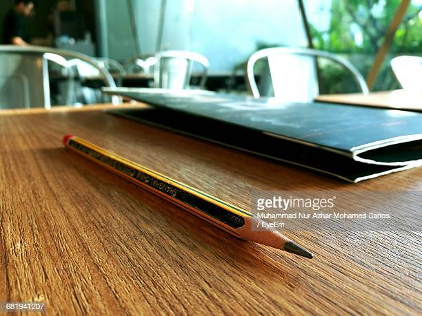 Close-Up Of Pencil And Menu Card On Table At Restaurant