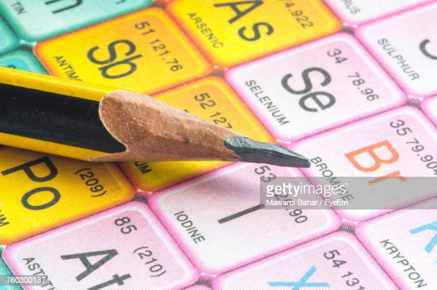 close-up of pencil on periodic table - periodic table stock photos and pictures