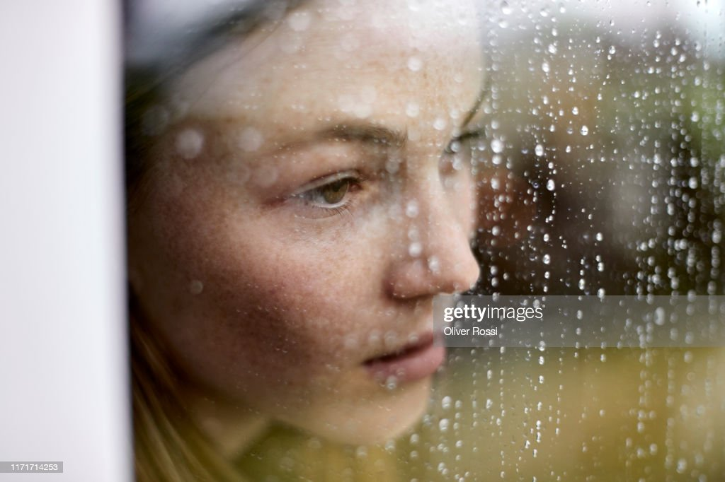 Close-up of pensive young woman looking out of window : Stock Photo