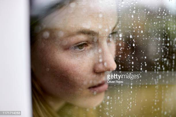 close-up of pensive young woman looking out of window - verdriet stockfoto's en -beelden