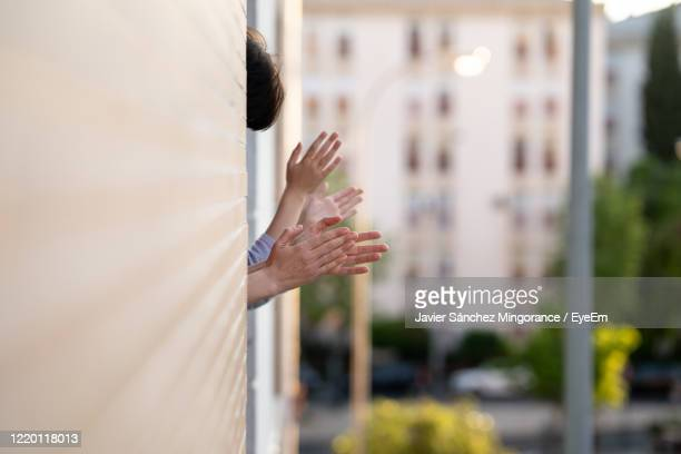 close-up of people applauding out of window - applauding stock pictures, royalty-free photos & images