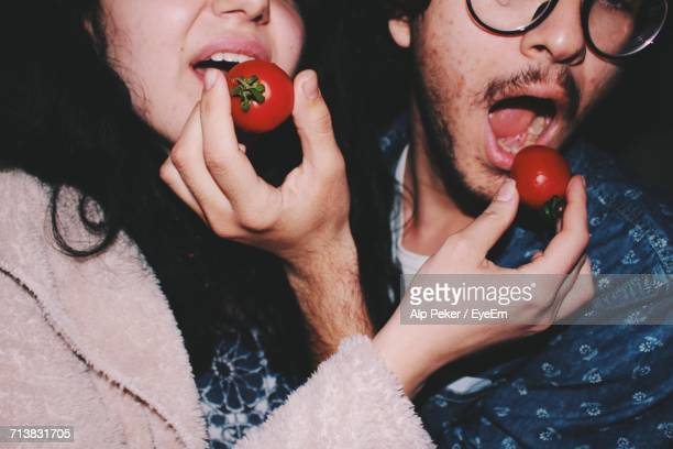 Close-Up Of People Eating Tomatoes