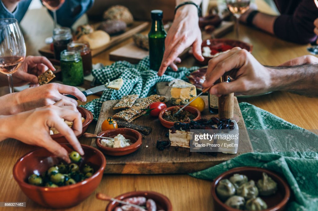 Close-Up Of People Having Food At Table : Stock Photo