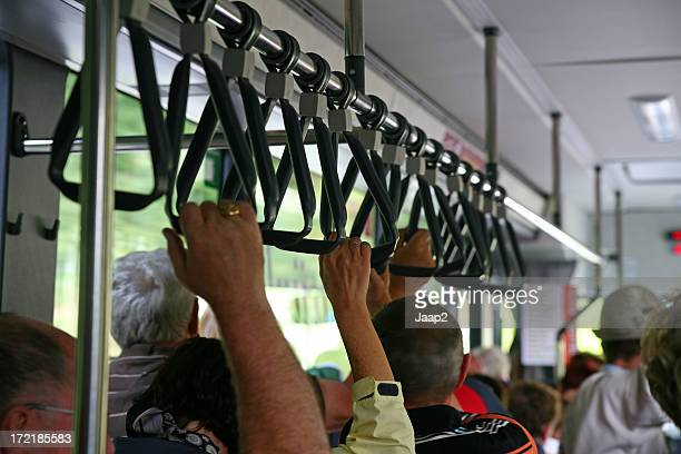 Close-up of people holding on while standing in a bus