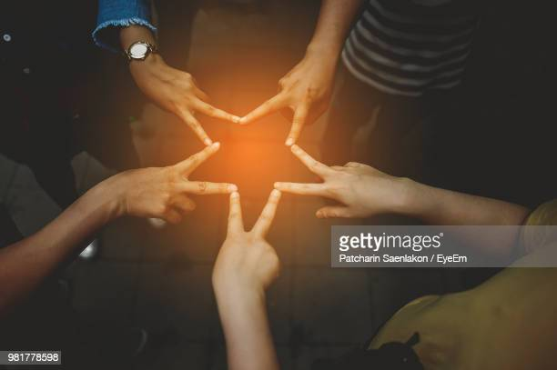 Close-Up Of People Making Star Shape With Hands