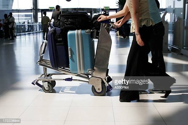 Close-up of people pushing a luggage rack at the airport