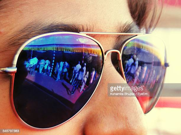 Close-Up Of People Reflecting In Sunglasses