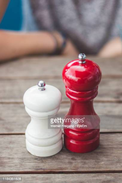close-up of pepper mills on table with person in background - pepper mill stock pictures, royalty-free photos & images