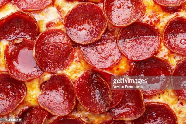 closeup of pepperoni pizza as a background - pepperoni pizza stock pictures, royalty-free photos & images