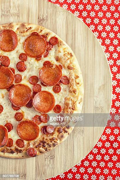 Close-up of Pepperoni Pizza on a bamboo table.