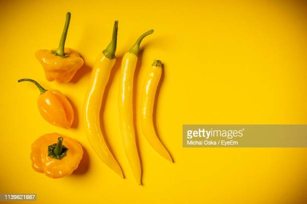 close-up of peppers on yellow background - yellow bell pepper stock pictures, royalty-free photos & images