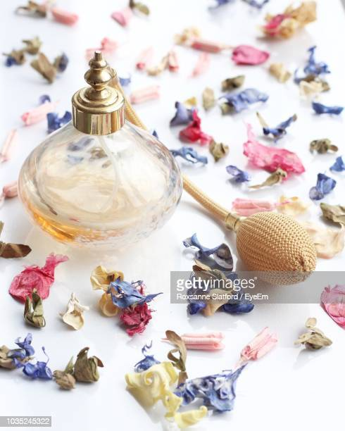 close-up of perfume bottle and petals on table - borough of lewisham stock pictures, royalty-free photos & images