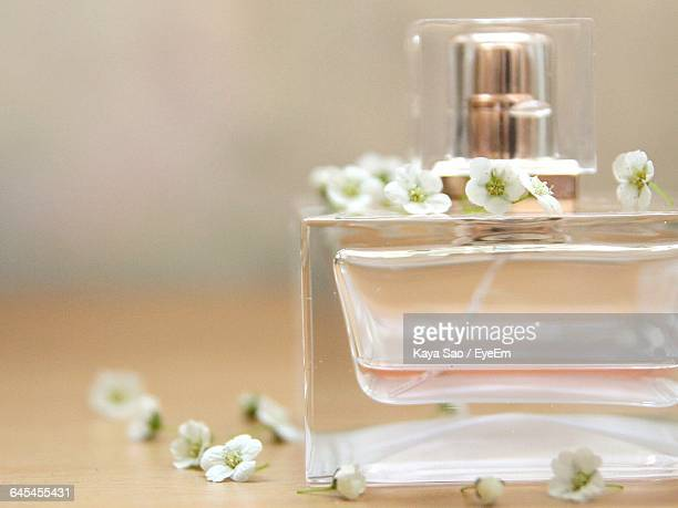Close-Up Of Perfume Sprayer With White Flowers On Table