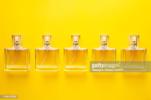 close-up of perfume sprayers on yellow background - perfume stock pictures, royalty-free photos & images