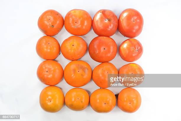 Close-Up Of Persimmons Arranged On White Background