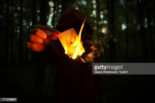 Close-Up Of Person Burning Ace Card In Forest