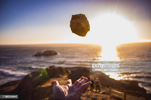 close-up of person catching rock at beach against sky during sunset - ephraim lem stock pictures, royalty-free photos & images