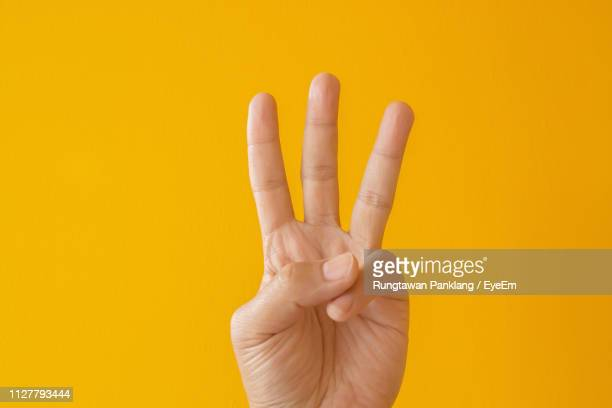 close-up of person hand gesturing against yellow background - three stock pictures, royalty-free photos & images