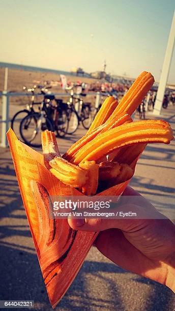 Close-Up Of Person Hand Holding Churros