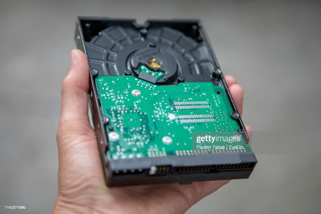 Close-Up Of Person Hand Holding Computer Circuit Board Against Gray Background : Stockfoto