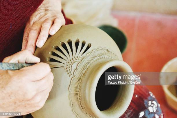 close-up of person hands carving on earthenware - carving craft product stock pictures, royalty-free photos & images